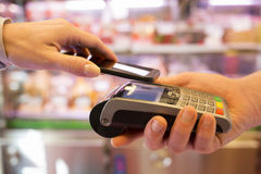 Kvinna som betalar med NFC-teknologi på mobiltelefonen, i supermarket Arkivbild