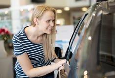 Kvinna som beundrar en bil på en auto show royaltyfri foto