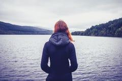 Kvinna som beundrar lugn av sjön royaltyfri fotografi
