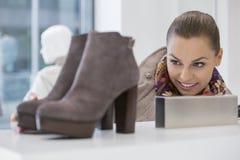 Kvinna som beundrar skodon i lager arkivfoto