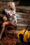 Kvinna som bevattnar med den trädgårds- slangen Arkivbilder