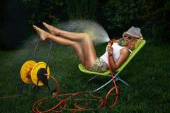 Kvinna som bevattnar med den trädgårds- slangen Royaltyfri Foto