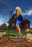 Kvinna som bevattnar med den trädgårds- slangen Arkivfoton