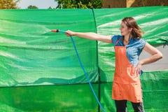 Kvinna som bevattnar trädgården med slangen Arkivfoto