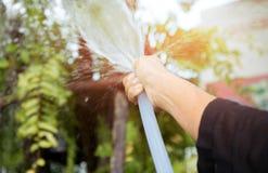 Kvinna som bevattnar trädgården med vatten för trädgårds- slang royaltyfria bilder