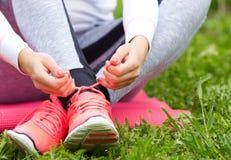 Kvinna som binder gymnastikskor på gräs Arkivbild