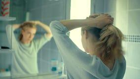 Kvinna som binder hennes långa blonda hår som vänder mot spegeln i hennes badrum stock video