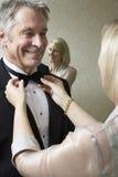 Kvinna som binder mans fluga Fotografering för Bildbyråer