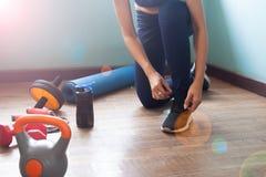 Kvinna som binder skor för övningen, sund livsstil arkivbilder
