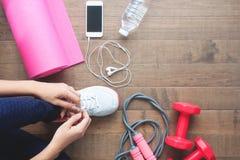 Kvinna som binder sportskor, sportutrustningar och mobila enheten fotografering för bildbyråer