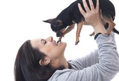 Kvinna som biter hennes chihuahua på vit bakgrund Royaltyfri Foto