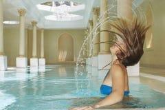 Kvinna som bläddrar hår i simbassäng Royaltyfri Foto