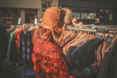 Kvinna som bläddrar omslag på marknaden Arkivbilder