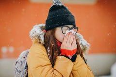 Kvinna som blåser hennes näsa in i näsduken Ung kvinna som får sjuk med influensa i en vinterdag royaltyfri bild