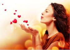 Kvinna som blåser hjärtor från händer Arkivfoto
