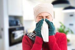 Kvinna som blåser inomhus hennes näsa som kallt influensabegrepp royaltyfri bild