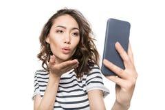 Kvinna som blåser kyssen, medan ta selfie på smartphonen Royaltyfria Bilder