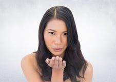 Kvinna som blåser kyssen mot den vita väggen Fotografering för Bildbyråer