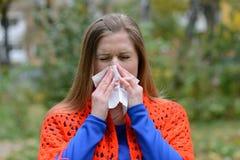 Kvinna som blåser näsan in i silkespapper royaltyfria foton