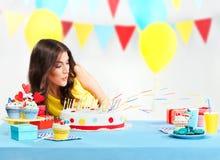 Kvinna som blåser stearinljus av kakan Arkivfoto
