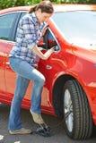 Kvinna som blåser upp bildäcket med fotpumpen arkivfoto