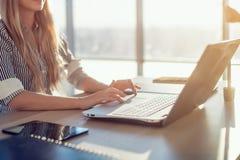 Kvinna som blogging i rymligt kontor genom att använda datoren på hennes arbetsplats Kvinnligt anställdsammanträde, le som ser ka arkivbild