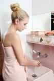Kvinna som blondinen i rosa washes för en handduk räcker Royaltyfria Bilder