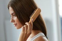 Kvinna som borstar härligt sunt långt hår med borsteståenden Royaltyfri Bild