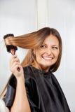 Kvinna som borstar hår i salong Arkivbild