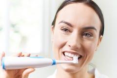 Kvinna som borstar tänder med den elektriska tandborsten i badrum Arkivfoton
