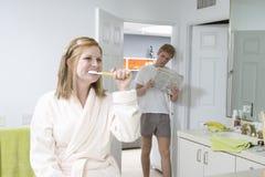 Kvinna som borstar tänder i badrum Arkivbild