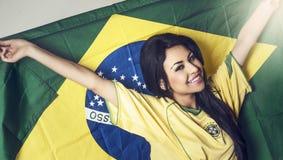 Kvinna som bär den Brasilien fotbollskjortan Arkivbild