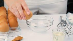 Kvinna som bryter ägg in i en glass bunke, ultrarapid stock video