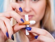 Kvinna som bryter cigaretten som blir av med böjelse Arkivbilder