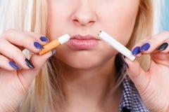 Kvinna som bryter cigaretten som blir av med böjelse Arkivfoton