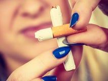 Kvinna som bryter cigaretten som blir av med böjelse Royaltyfri Foto