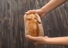 Kvinna som bryter nytt smakligt bröd på träbakgrund fotografering för bildbyråer