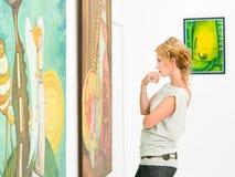 Kvinna som contemplaing färgrika målningar Fotografering för Bildbyråer