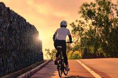 Kvinna som cyklar den stigande vägen Fotografering för Bildbyråer