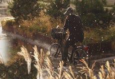 Kvinna som cyklar i regn med rainwearen - regn tappar fallande skurkroll royaltyfri bild