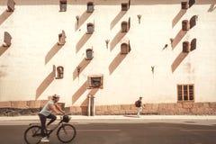 Kvinna som cyklar på cykeln och gångare av den historiska svenska staden Arkivfoton