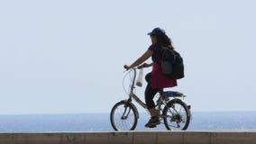 Kvinna som cyklar på den trevliga invallningen, turism och sporten, aktiv livsstil Långsam-Mo stock video