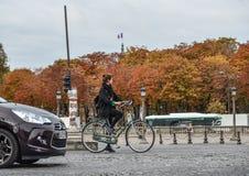 Kvinna som cyklar på gatan av Paris, Frankrike royaltyfria foton