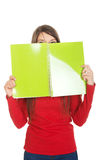 Kvinna som döljer hennes framsida bak en anteckningsbok Royaltyfri Foto