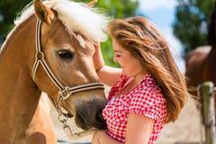 Kvinna som daltar hästen på ponnylantgård Arkivbilder