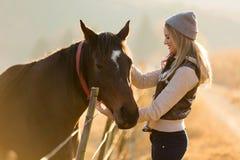 Kvinna som daltar hästlantgården Royaltyfri Fotografi