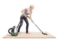 Kvinna som dammsuger en matta med dammsugare Royaltyfri Fotografi