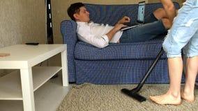 Kvinna som dammsuger, man som lyssnar till musik på bärbara datorn som vilar på soffan stock video