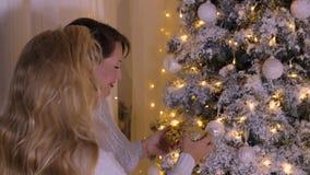 Kvinna som dekorerar träd för nytt år för att fira som är festligt i hemtrevligt hem lager videofilmer