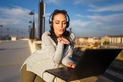 Kvinna som direktanslutet överför kyssar vid den utomhus- bärbara datorn Royaltyfria Bilder